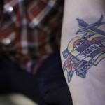 Detail shot of Nate Myrick's tattoo of 1 John 4:19