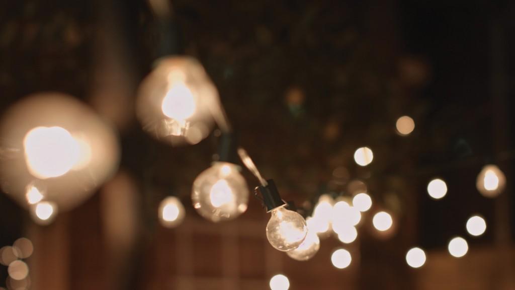Bistro lights illuminate a backyard at dusk