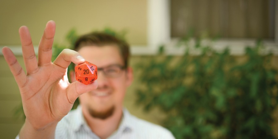 Fuller Seminary grad Joe Stroup holding an orange gaming die