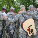 Fuller Seminary alum Jason Hohnberger praying with other soldiers