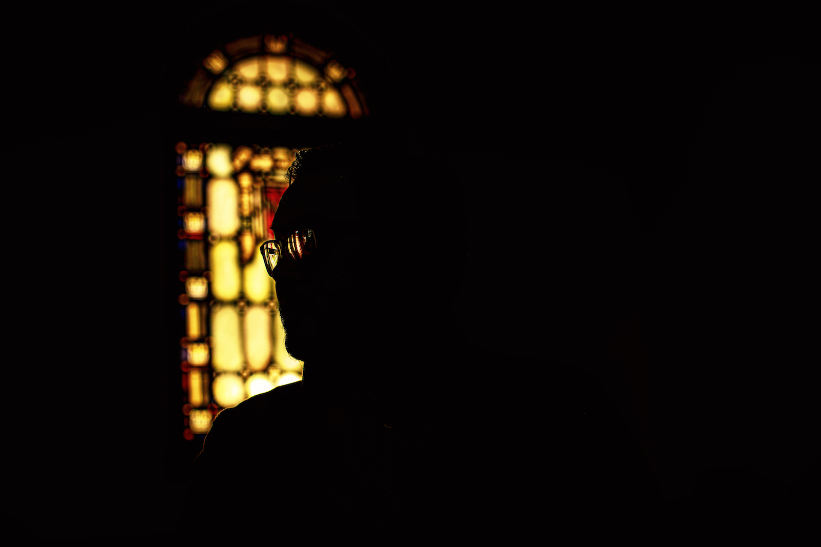 sillouette of man in front of stained glass window